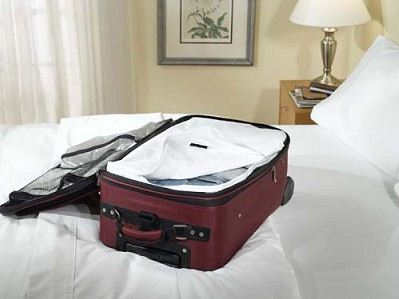 Picture of red, open suitcase on bed. The suitcase has a bed bug proof luggage liner in it.