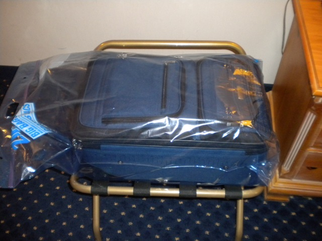Blue suitcase in a ziplock plastic bag to protect from bed bugs